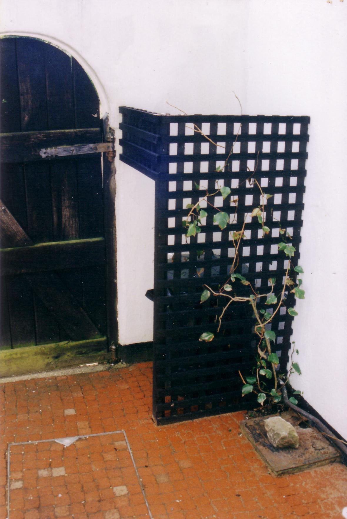 Bin hidden by garden panel